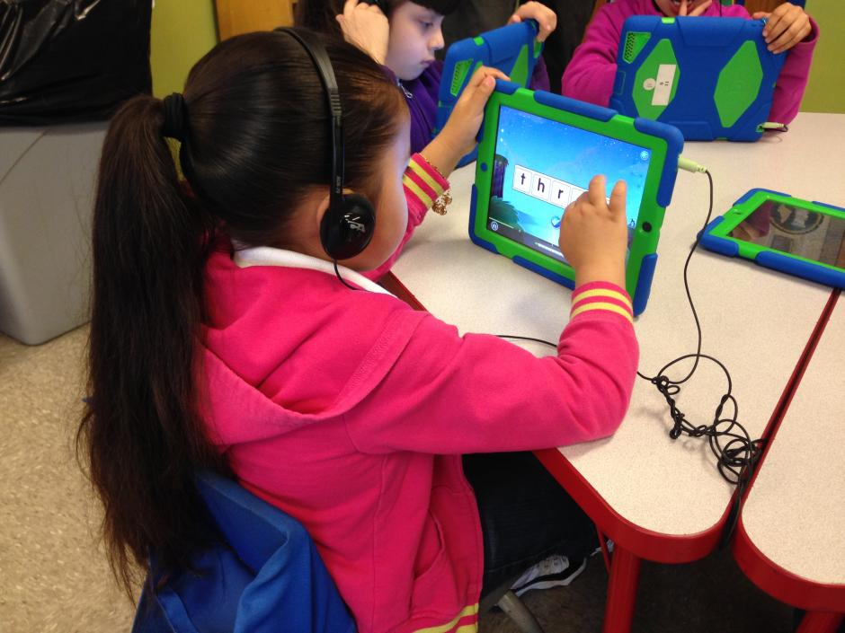 A student in a kindergarten classroom at the Cesar E. Chavez Multicultural Academic Center in Chicago uses a tablet to learn letters of the alphabet through sound. (Carolina Astrain for EWA)