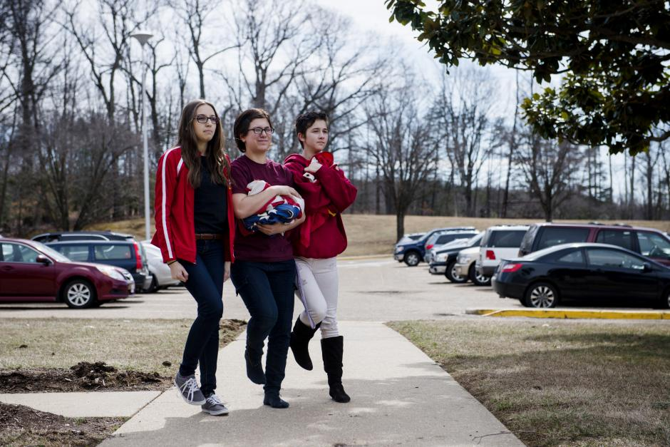 From left: Meghan Meza, Meghan Jones, and Summer Gilliard, return to the school after lowering the flags at Quantico Middle/High School on March 13, 2015 in Quantico, VA.  (Amanda Voisard for The Hechinger Report)