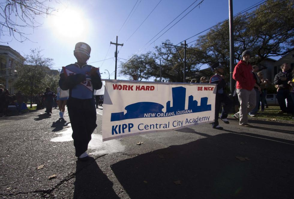 Students march in parade holding a KIPP Central City Academy banner.
