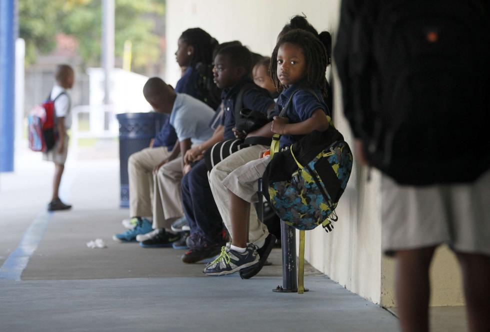 Kindergartner Tyree Parker sits at the front doors of Maximo Elementary as he waits for school to open. (Tampa Bay Times/Dirk Shadd)