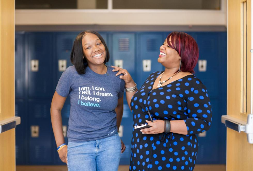 A OneGoal student Fellow, left, and Program Director teacher Ms. Jones chat in the hallway of their Atlanta high school.