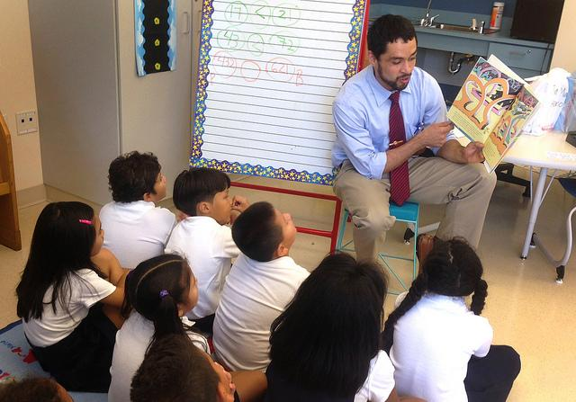 Teach For America teacher and Penn State graduate Sergio Santiago reads a book to his students at a Washington, D.C. elementary school. (Flickr/PennState)