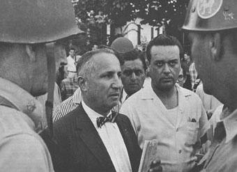 "Benjamin Fine of the New York Times, one of EWA's founders and its first president, center, covers the racial integration of schools in Little Rock, Ark., in September 1957. ""Mobs don't like reporters. At least, the Little Rock mobs didn't,"" Fine wrote in an account of his experience published in the Fall 1957 edition of EWA's quarterly newsletter, The Education Beat."