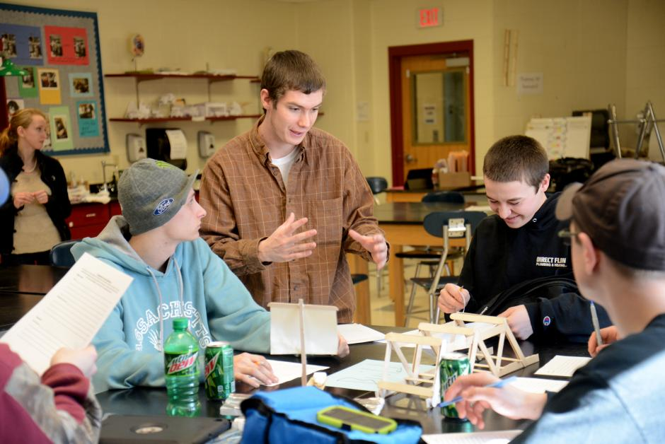 Ryan Marquis, center, guides his classmates through an engineering project he designed as part of his work-study internship. (Jim Vaiknoras for The Hechinger Report)